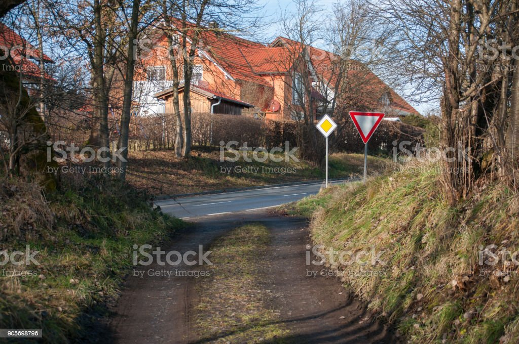 A give way yield sign at a country dirt road intersection stock photo