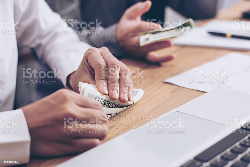 Giving a bribe into a pocket to negotiate business. Closeup shot stock photo