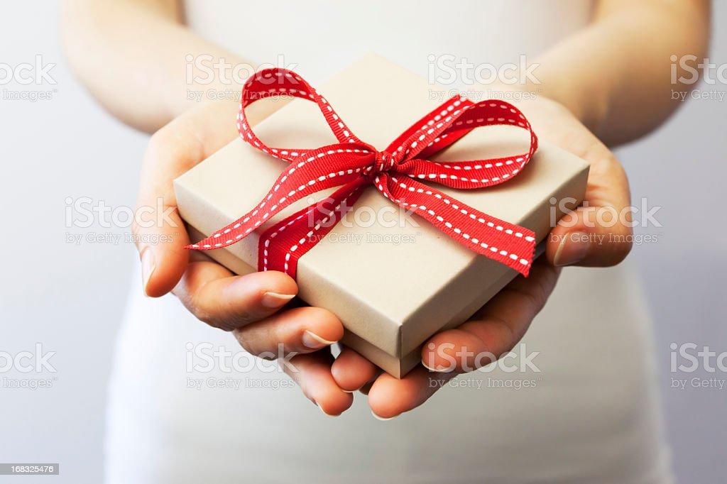 Giving a gift A person holding a gift box. Adult Stock Photo