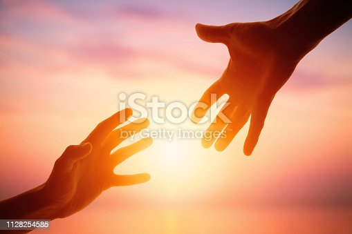 Giving a helping hand on the background of the dawn. Social life