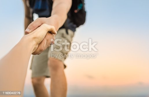 Hiker giving his hand helping partner climb up to the top of mountain.