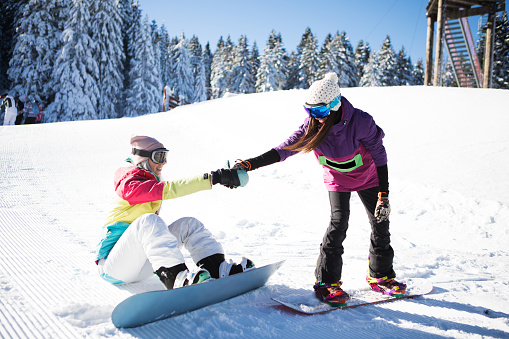 Giving a helping hand to snowboarding friend