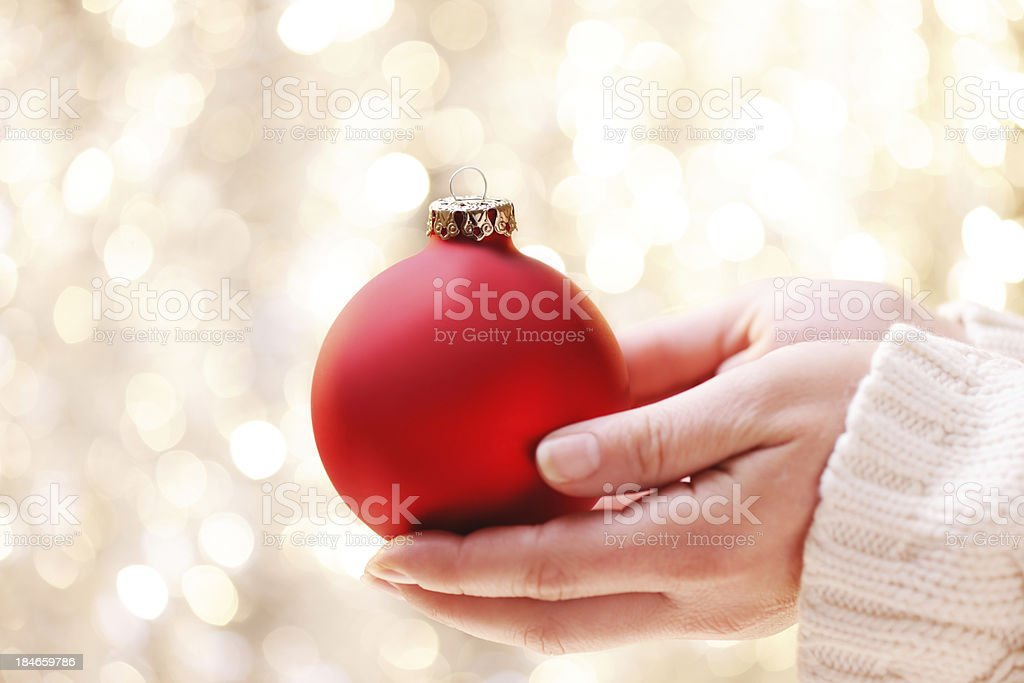 Giving a red christmas bauble royalty-free stock photo