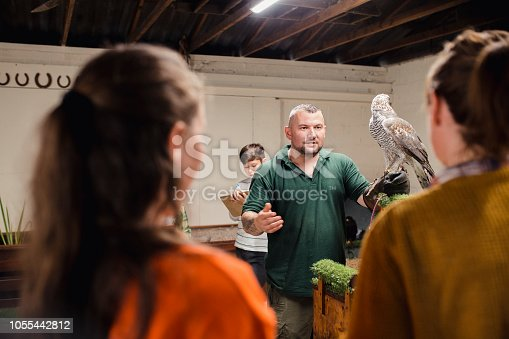 Over the shoulder view of a student and her teacher standing listening to a falconer while he discusses the goshawk.