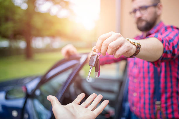 Giving back car keys Man standing by the car and giving back car keys car key stock pictures, royalty-free photos & images