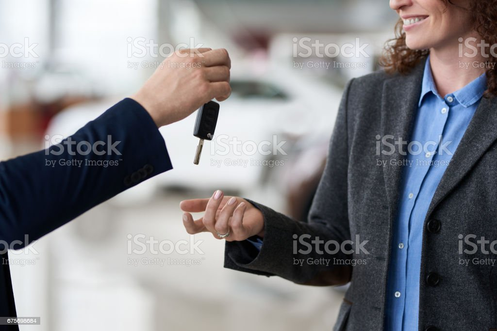 Giving car key to new owner stock photo