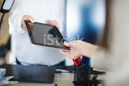 Giving digital tablet to colleague over the desk in the office