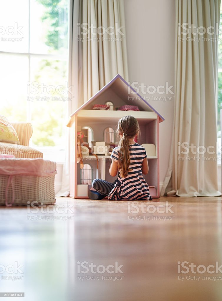 Giving her dolls a place to call home stock photo
