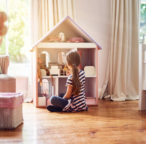 Giving her dolls a place to call home Rearview shot of a little girl playing with her dollhouse while sitting on her bedroom floor girl bedroom stock pictures, royalty-free photos & images