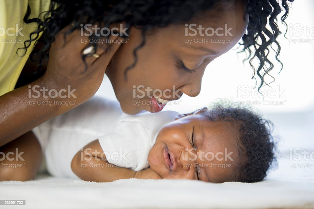 Giving Her Newborn Baby a Kiss stock photo