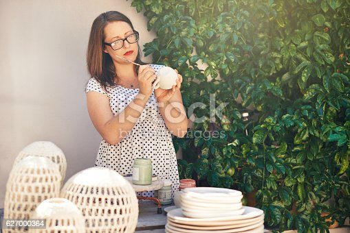 627000458istockphoto Giving her wares the finishing touch 627000364