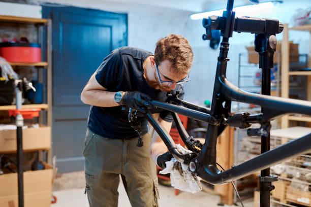 darle a su bicicleta un poco de tlc - bastidor de la bicicleta fotografías e imágenes de stock