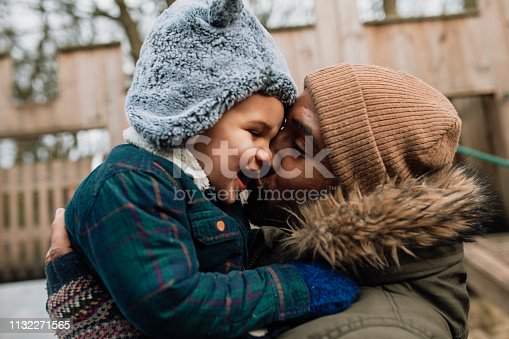 Dad and his son in the park during winter time. He is holding his son in his arms and giving him a kiss on the cheek.