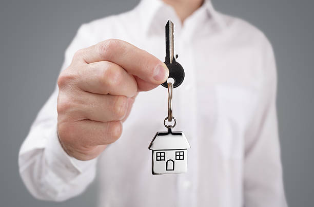 Giving house key on keychain stock photo