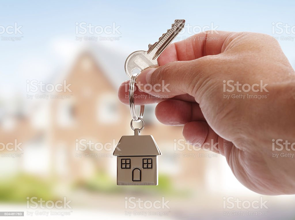 Giving house keys Holding house keys on house shaped keychain in front of a new home Adult Stock Photo