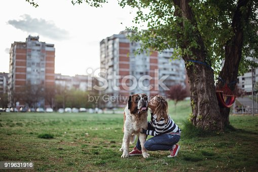 Lovely and cute woman spending her leisure time at the park with her Bernard dog.