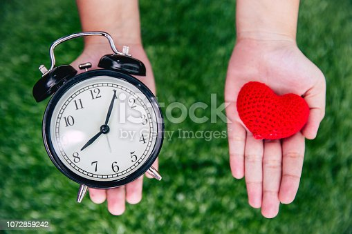 giving love times heart and clock on girl hand.