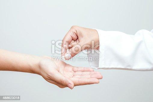 istock Giving Medicine to Patient 488623018