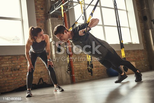 istock Giving motivation. Young and strong man in sportswear doing push ups with trx fitness straps and smiling while his personal trainer is standing close to him. 1162483593