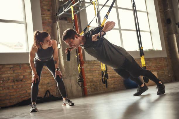motivatie geven. jonge en sterke man in sportswear doet push-ups met trx fitness bandjes en glimlachend terwijl zijn personal trainer dicht bij hem staat. - personal trainer stockfoto's en -beelden