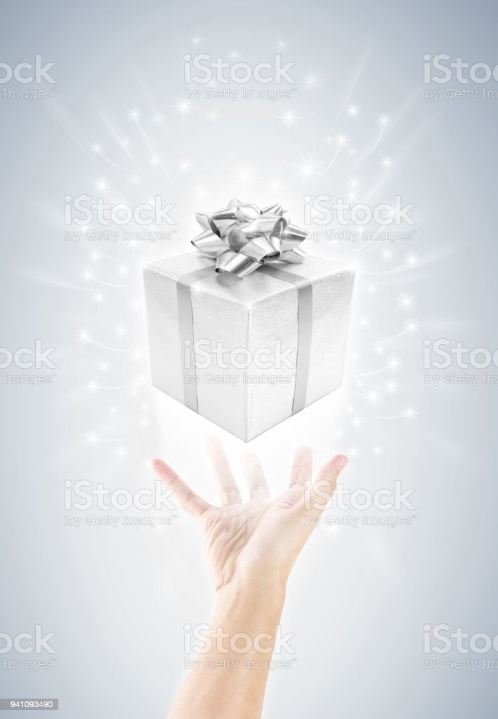 giving or carrying hand with silver celebrate gift box and migic...