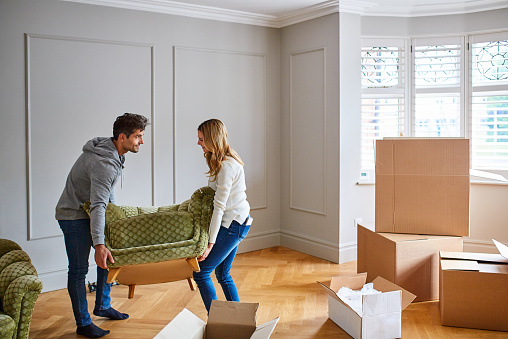 Shot of a young couple moving a couch into their new home