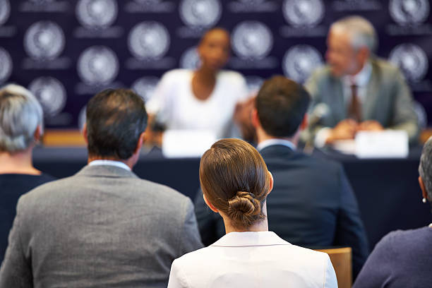 Giving their statement to the public Shot of a group of businesspeople in a press conference debate stock pictures, royalty-free photos & images
