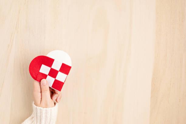 dar el concepto del martes con las manos de la mujer sosteniendo el corazón rojo y blanco, concepto del día de la caridad - giving tuesday fotografías e imágenes de stock