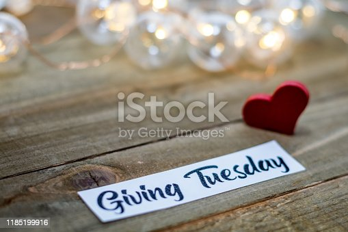 Giving Tuesday donate charity concept with text and cash and or credit cards on wooden board
