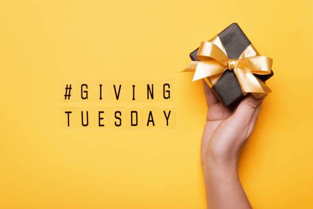 давать вторник. глобальный день благотворительности после черной пятницы торговый день. женщина стороны проведения подарочная коробка на  - giving tuesday стоковые фото и изображения