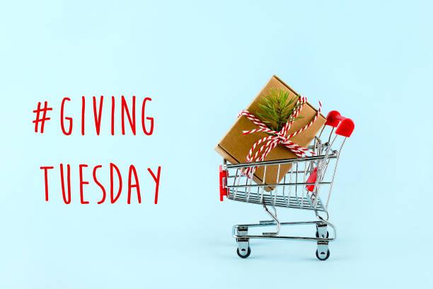 dar las vacaciones del martes. carro con caja de regalo. caridad, concepto de donaciones. - giving tuesday fotografías e imágenes de stock
