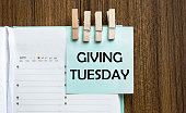 Giving Tuesday notes paper and a clothes pegs on wooden background