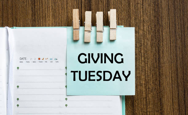 giving tuesday notes paper and a clothes pegs on wooden background - giving tuesday стоковые фото и изображения