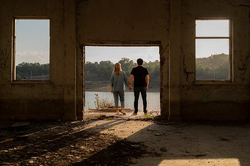 göl kenarında bulunan harabede göl manzarası izleyen çift. Ters ışıkta arka taraftan görüntülenmişlerdir.