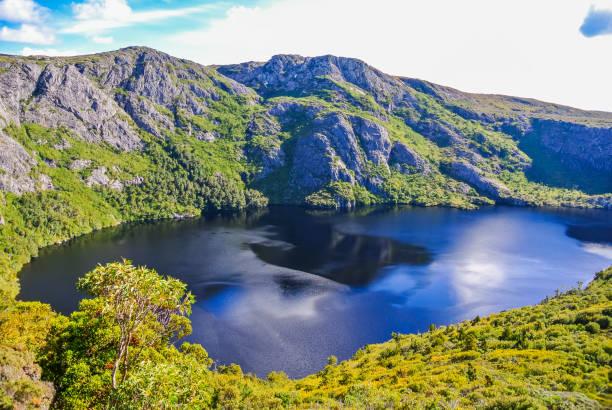 glacial lake and rugged mountains at cradle mountain, tasmania - cradle mountain stock photos and pictures