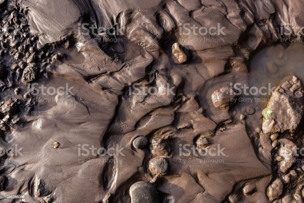 Glacial riverbank shore with wet black silt sand mud stock photo