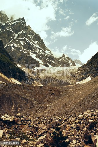 Glacier against the backdrop of the mountain peaks and the blue sky. The Chalaadi Glacier, Georgia, Caucasus. Vintage image.