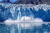Distant view of tidewater glacier calving into Glacier Bay National Park, with large splashes of water and ice.