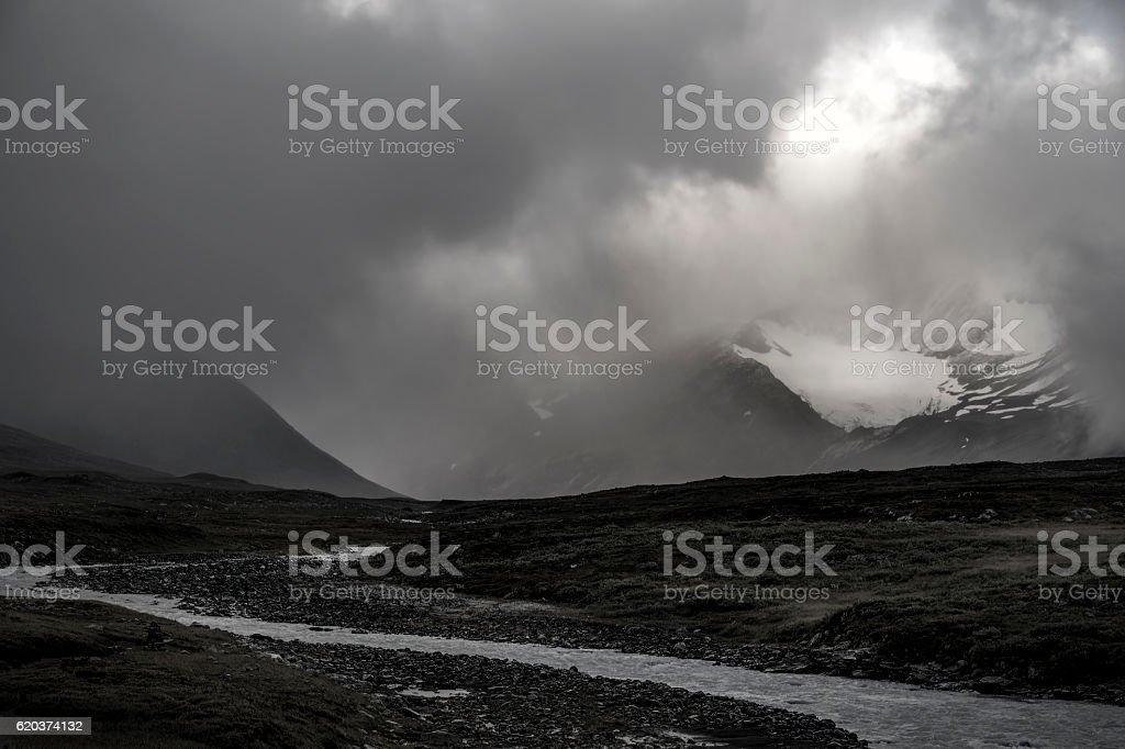 Glacier covered sun lighted mist river landscape black and white foto