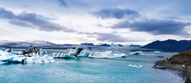 Glacier Lagoon, Iceland: People Walking Near Lagoon with Icebergs Glacier Lagoon, Iceland: People walking along the edge of Glacier Lagoon—known locally as Jökulsárlón—in September. glacier lagoon stock pictures, royalty-free photos & images