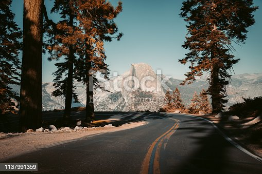 Beautiful view of winding Glacier Point Road with famous Half Dome summit in golden evening light at sunset, Yosemite National Park, California, USA