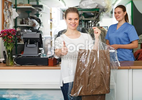 istock Glad client of laundry holding clean garment 985125840