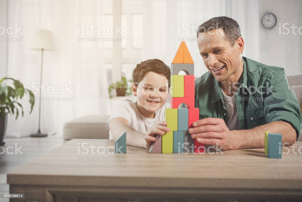 Glad father and son constructing house from small details stock photo