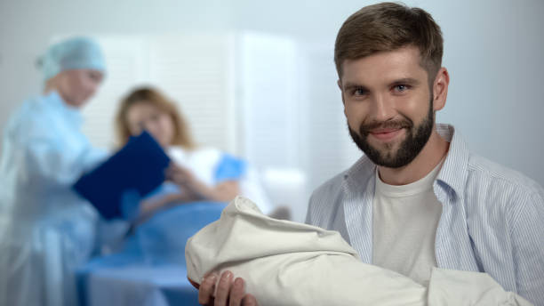 glad father holding newborn, obstetrician explaining mother how to breast-feed - woman breastfeeding husband stock photos and pictures