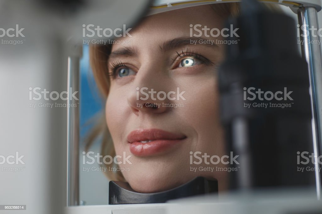 Glad female examining eyesight with equipment stock photo
