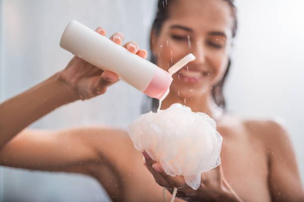 frohe weibliche pressung von flüssigkeit auf badeschwamm - sonnendusche stock-fotos und bilder