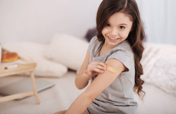 Glad girl applying medical patch on the arm at home stock photo