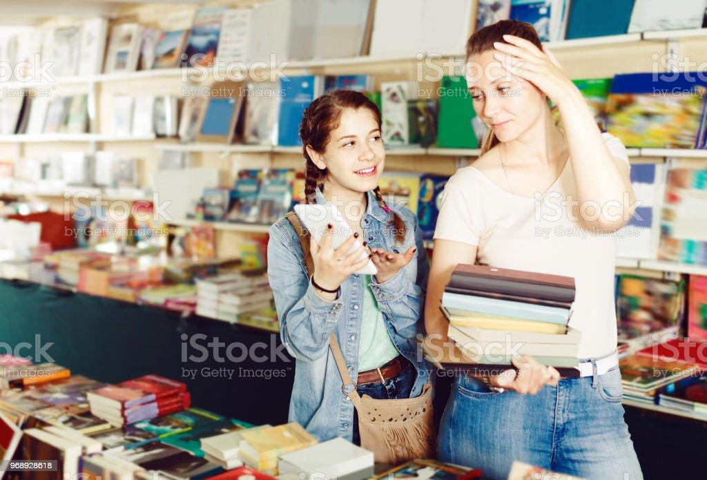 menina feliz conversando sobre o tablet de tela e escolhendo livros de literatura com a mãe - foto de acervo