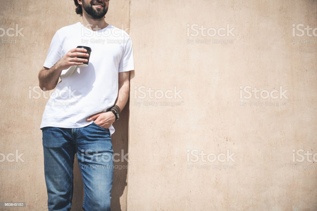 Glad guy enjoying hot drink on the street - Royalty-free Adult Stock Photo