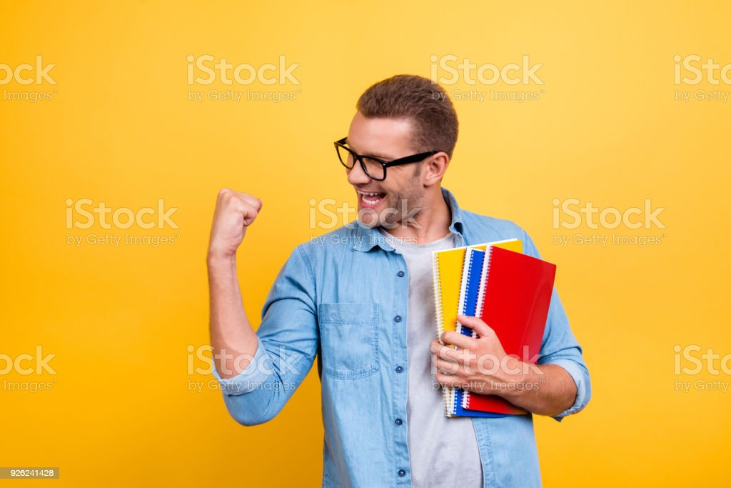 Glad guy raising his hand with fist having good mood celebrating victory, passes exams, completed work, holding three colorful copy books standing over yellow background stock photo